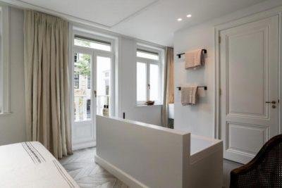 Witte slaapkamer met en suite badkamer - DSTRCT