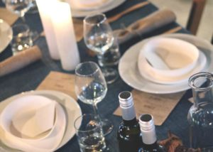 Tafel gedekt met wijn op diepblauw tafelkleed - Hutspot
