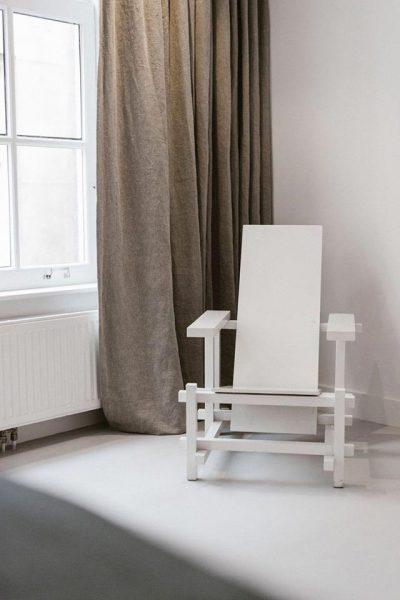 Witte stoel contrasteerd met een donker gordijn