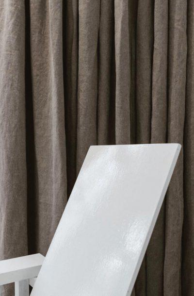 Witte stoel voor een donker gordijn