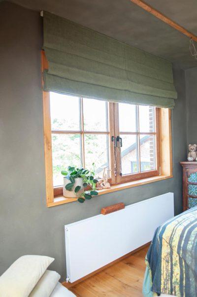 Diep groene slaapkamer met groene vouwgordijnen