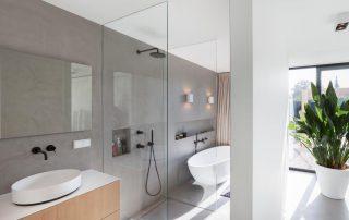 Moderne badkamer met betonciré muren en linnen gordijnen