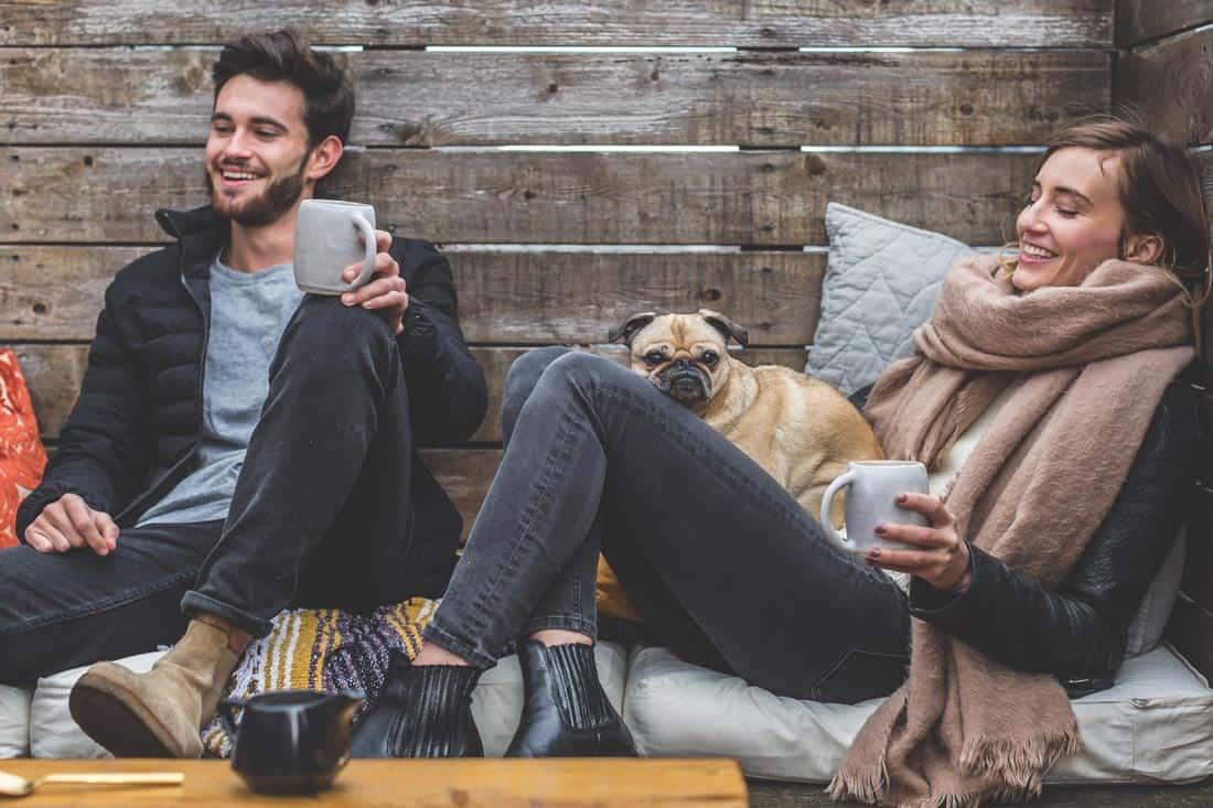 Man en vrouw op het terras met een hond op schoot