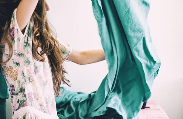 Vrouw in bloemetjesjurk tilt een lap stof op