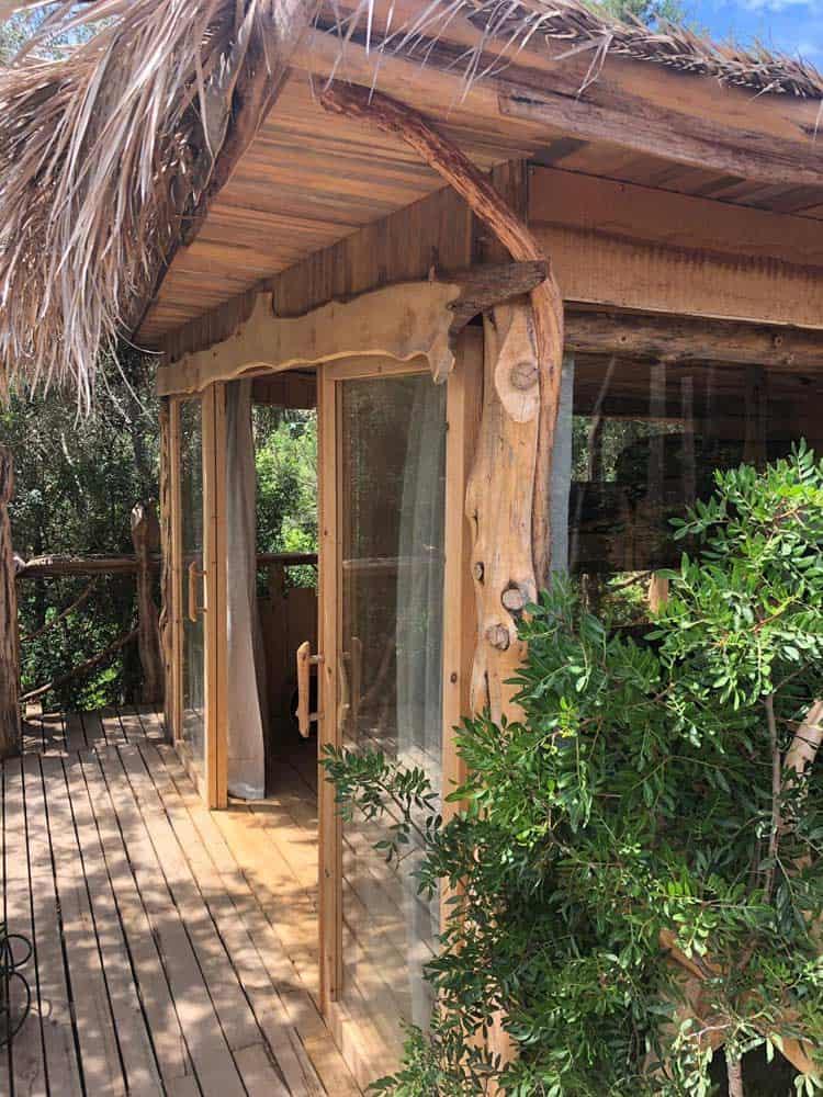 Ingang met open schuifpuien en palmbladeren op het dak