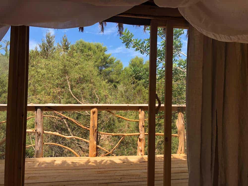 Vanuit binnen naar buiten kijken door open schuifpuien met beige gordijnen en bomen