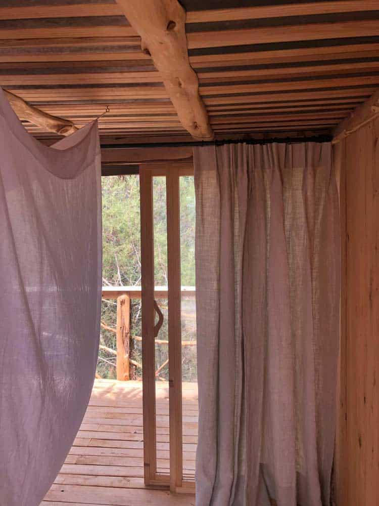 Houten interieur in boomhut met beige gordijnen