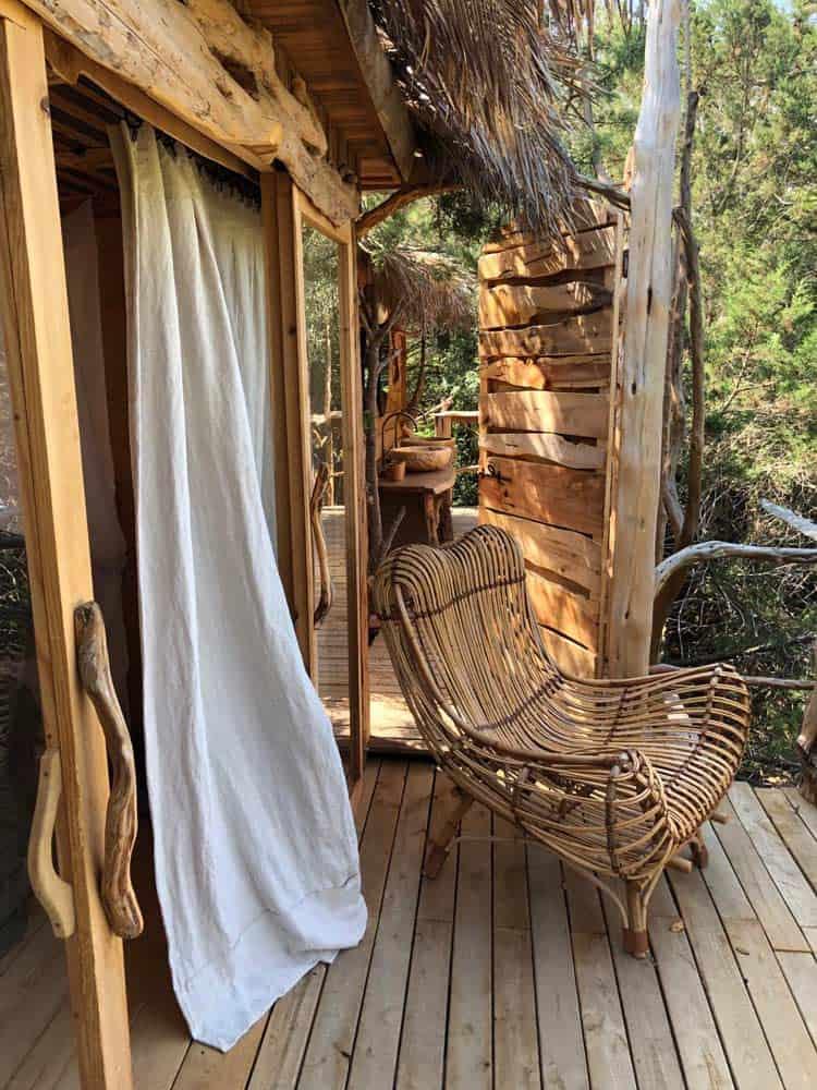 Beige gordijnen die naar buiten waaien met houten stoel op veranda boomhut