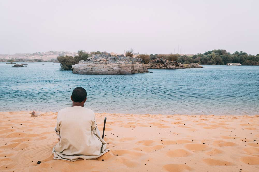 Egyptian man in clothing sitting near the water