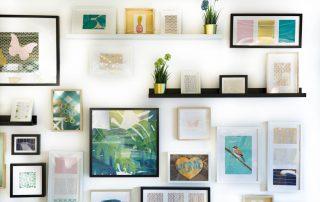 Een verzameling fotolijsten aan de muur