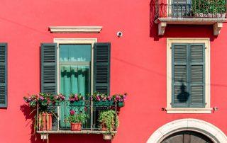 Balkon met planten en een rode gevel