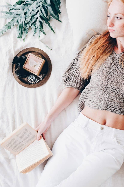 Vrouw liggend op het bed met een boek in haar hand