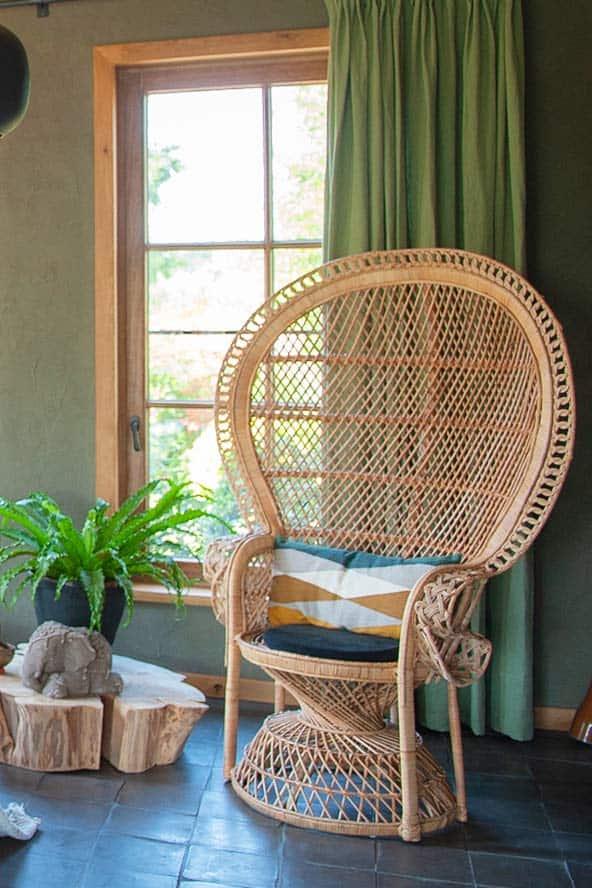 Een rotan stoel en groen gordijn.