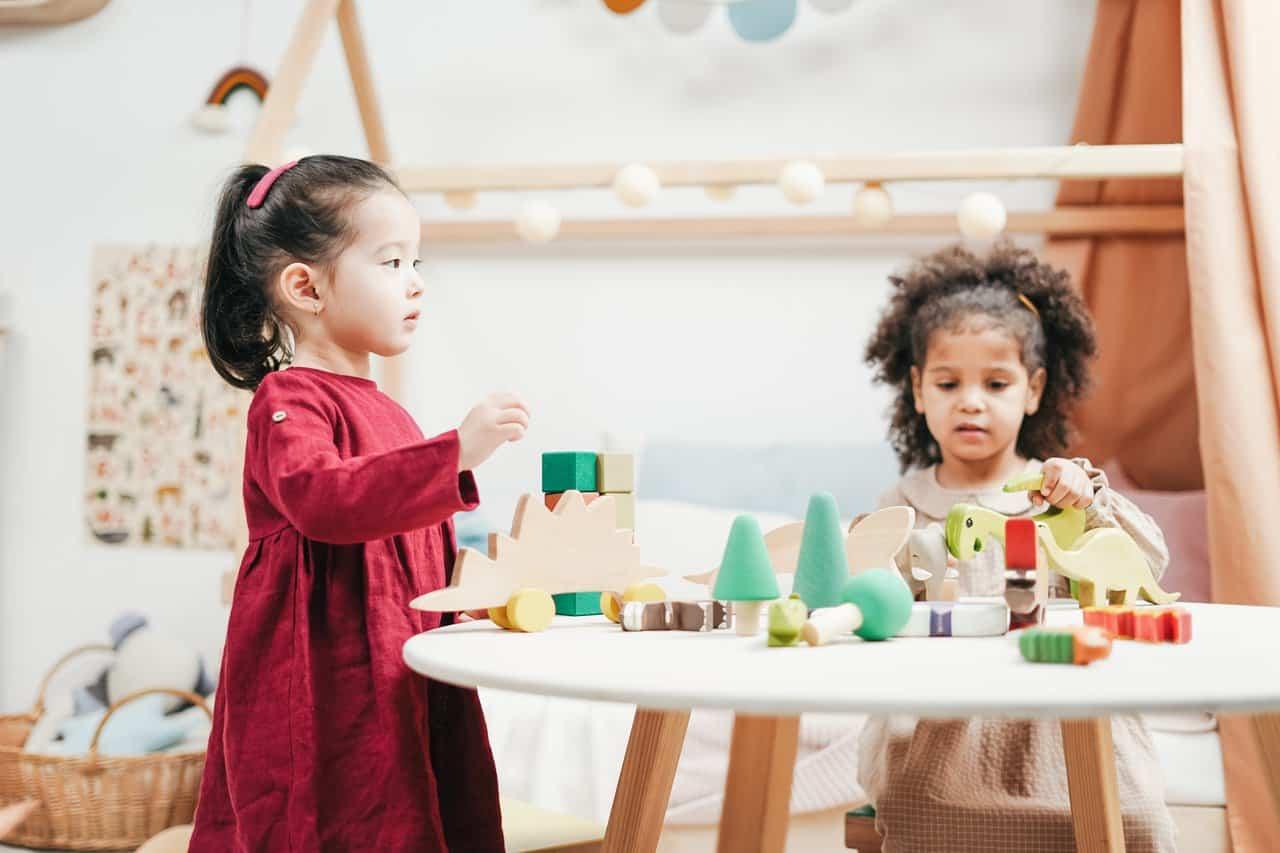 Kinderen met speelgoed in een neutrale kinderkamer
